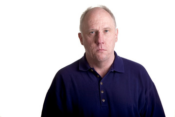 An older bald guy in a blue shirt with a serious expression