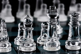 Glass chess pieces on glass board