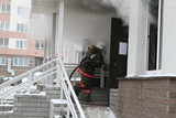 Firefighter pulling hose into blazing building