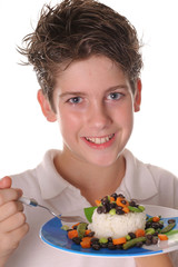 young boy eating healthy rice, beans & veggies vertical