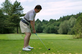 Golfer addressing the ball as he is about to tee off poster