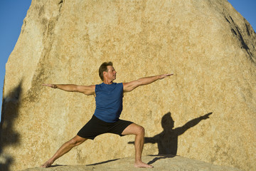 A man practices yoga on the boulders in Joshua Tree.