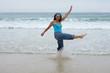 Beautiful girl splashing water on the beach