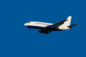 passenger jet in flight  clear blue sky  landing gear down