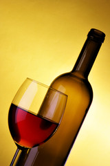 Glass and bottle of red wine over yellow background