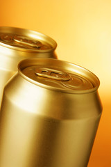 Golden beer cans close-up over yellow background
