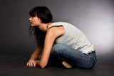 The dark-haired girl sitting on a floor it was bent forward poster