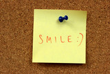 Sticky note on a bulletin board. Happy message: smile poster