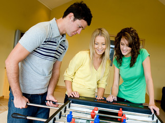 Three friends playing table football at home