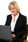 Attractive 40 something woman sitting in chair with laptop.