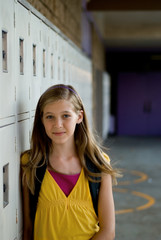 Cute preteen, teen or tween blonde standing against her locker.