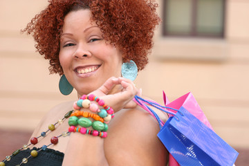 Plus size model, smiling, with shopping bags