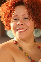 female with short curly red hair and bright jewelry