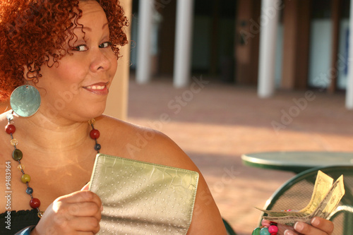 female with red curly hair, colorful jewelry and a wallet