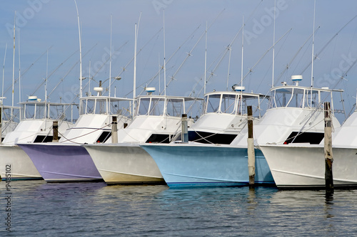 Row of nice deep sea fishing boats in a marina.