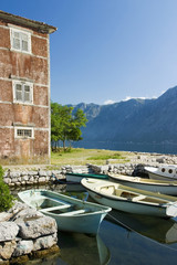 Boka Kotorska Bay landscape with old house and wooden boats