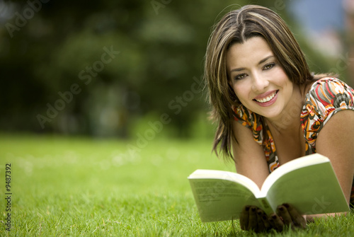 Beautiful girl reading a book - lying on the floor outdoors
