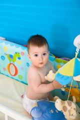 Cute baby boy ( 1 year old ) playing in baby bed