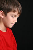 Young boy with downcast eyes in casual attire poster