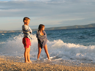Kids playing on Adriatic sea coast in sunset, naer Tucepi