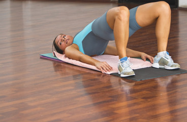 Young woman doing floor exercise in a gym.