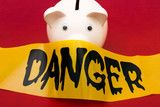 Pink piggy bank with danger tape , dangerous investments poster