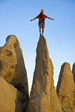 A climber silhouetted on the summit of a rock spire. poster