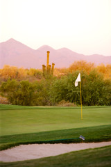 Golf course Arizona desert with mountains late afternoon sun