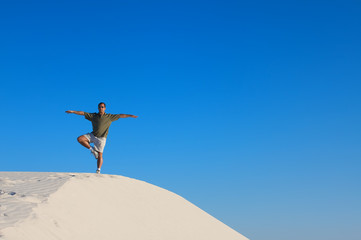Man in a yoga tree pose on top of a sand dune
