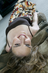 Smiling woman lying backwards on the floor
