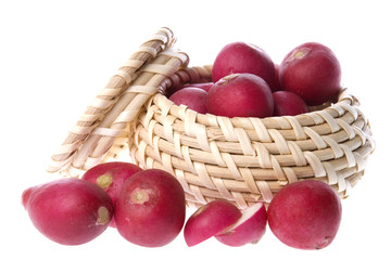 Isolated image of red radish in and around a basket.