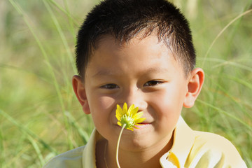 Child sniffing a yellow flower