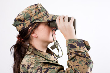 The attractive girl in a camouflage with a binoculars