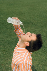Man pouring water into his mouth
