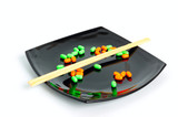chemical diet - colored pills on black plate and chopsticks poster