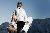 Macho snowboarder with adoring lingerie clad female fan poster