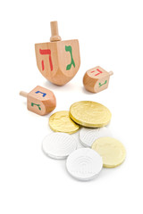three wooden dreidel and chocolate coins gelt isolated on white