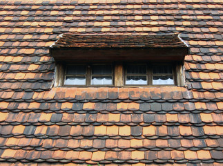Old-style roof window in a shingled roof