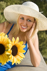 A beautiful young blond woman carrying a basket of sunflowers