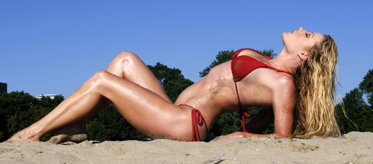 Pretty woman in red bikini arching her back