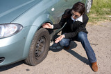 woman and the car with punctured wheel poster