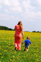 Young woman with her son outgoing in dandelion field