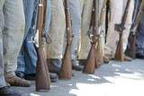 Civil War re-enactors  with period guns stand in a row. poster