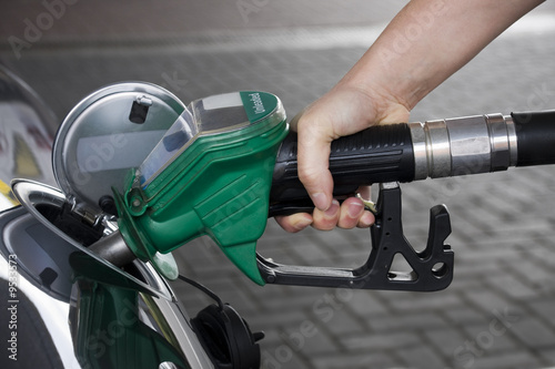 Hand holding green fuel pump refuelling a car