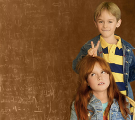 Red headed girl and blond boy in front of a blackboard