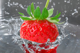 Strawberry entering water and making splash-