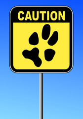 yellow and black caution sign with paw print on blue sky