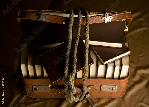 Old torn suit-case full of books and a rope holding it together