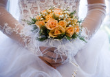 The bride holds a bouquet of yellow roses