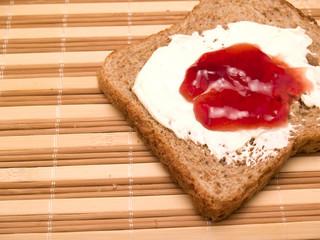 rodaja de pan negro con queso y mermelada
